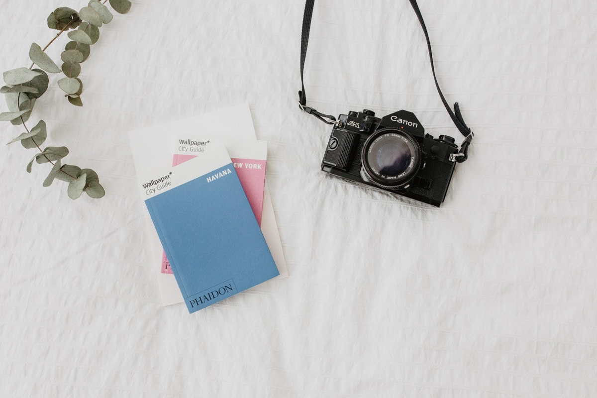 Ten easy steps on how to prepare your trip when you fly abroad - Flat lay composition with travel guides and old camera